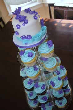 I made this for a wedding shower and was asked to make it in the purple and teal colors with flowers and butterflies.  I really like how the color combination worked out.  There are lemon cupcakes with a lemon curd filling, vanilla cupcakes with a strawberry filling and chocolate cupckaes with a rasberry filling.  They are all iced in a vanilla meringeu buttercream.  The cake on top is a 4 inch mini cake.  All decorations were made with MMF.