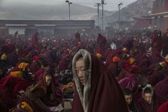 Tibetan Buddhist nuns try to keep warm in sub-zero temperatures before a chanting session. (Kevin Frayer/Getty Images)-Stunning photos from Tibetan Buddhists' Bliss Dharma Assembly - The Washington Post