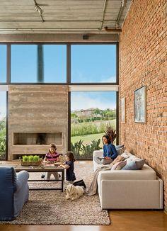 Sala de estar   Ao redor da lareira de concreto aparente, os painéis de vidro temperado de 10 mm deixam ver a paisagem. A proprietária Laura está no sofá da Artefacto com manta e almofadas da Empório Beraldin, Celina Dias e Dialma Brown. (Foto: Edu Castello/Editora Globo)