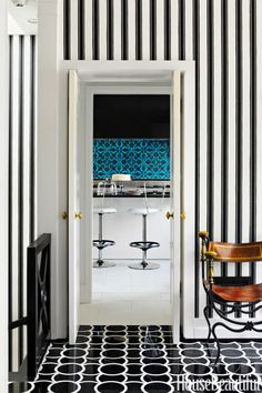 """Graphic patterns extend from the foyer in a Washington, D.C. town house through to the kitchen. """"We both like snappy architectural solutions — like the patterned floor and striped wallpaper — that give black-tie panache to small spaces,"""" designer Jeff Lincoln says of the house he designed with Hillary Thomas. The black and white of Montgomery 1 marble floor tiles by Ann Sacks and Block Print Stripe wallpaper by Farrow & Ball is reminiscent of Dorothy Draper."""
