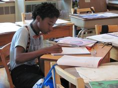 Grade 8 student working on his lesson book.