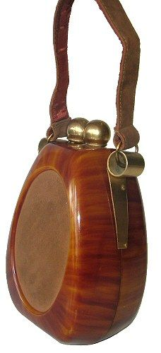 Art Deco 1940s Bakelite handbag, shaped like a pear, features a catalin Bakelite body sometimes known as phenolic in a toffee caramel color. To the center is a suede oval (both sides) with brass clasp and trim. Via deco-world.co.uk/.