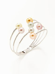 Multicolor Pearl Asymmetrical Bangle    Color: pearl    Gilt Price  $3,889        Style Information      8 x 11mm multicolor freshwater cultured pearl and 18K white gold asymmetrical bangle bracelet with round cut diamond details  * Total diamond carat weight is 0.24  * Diamond color is G-H  * Total diamond clarity is SI  * 2.25 inches in diameter  * 1.35 inches at widest point  * Hinge closure    Brand: Tara Pearls    Color: pearl    Material: Pearl, 18K white gold, and diamond    Origin…