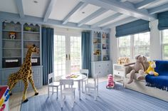 Blue boy's room with blue built-in cabinets flanking French doors covered in blue curtains on brass drapery rods.