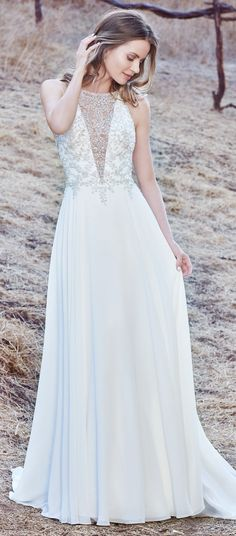 Maggie Sottero - MAREN, This sleeveless sheath wedding gown features a bodice accented in Swarovski crystals and delicate beading, creating an illusion jewel over deep V-neckline and illusion open back. A Revina Chiffon skirt completes the elegant romance of this look. Finished with crystal buttons over zipper closure.