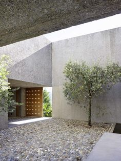 A simply cut monolith in washed concrete, which is docked directly to the road, rises from the natural topography of the slope.  Two cars are parked almost directly on the roof.  The visitor is guided down along a linear alleyway to the entrance door...