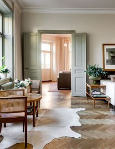 classic floors and architecture with sage green trim and mid-century furnishings…