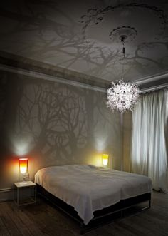A light sculpture that creates a tangle of tree branches and vines on the walls and ceiling