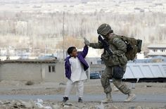 U.S army soldier takes five with an Afghan boy
