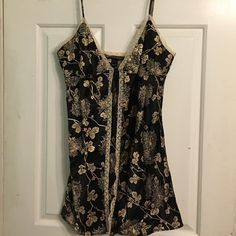"""Open Front Black & Gold VS Teddy Lingerie Excellent condition. Lace lined opening from tie on chest. Spaghetti straps. Black with gold flowers. 100% polyester. No panties included. Bust measures 17"""" armpit to armpit (could probably go a little larger depending on where you tied the tie at chest), 22"""" armpit to hem, and 31"""" shoulder to hem. Victoria's Secret Intimates & Sleepwear Chemises & Slips"""