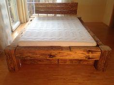 Balkenbett aus altem Holz mit Bettkästen