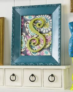 Create personalized wall art with an old budget frame, fabric and Mod Podge. I added Mod Podge Pearlized Sealer for an extra special touch.