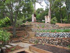 jardin en pente avec terrassement en pierre naturelle et marches en bois massif