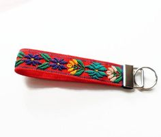 Beautiful fabric keychain made from handwoven Guatemalan textile. This woven key fob wristlet is great for having easy access to your key, Just slip it around your wrist to keep keys in reach while you multi-task. Woven with bold colors, print and texture, these pretty floral keychains are practically a work of art to wear. The vibrant colors and floral patterns are perfect for the boho style as well. Unique fabric key fobs make wonderful gifts for teachers! Woven on an orange base with a…