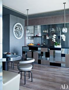 The symphony of reflective surfaces in the kitchen includes the polished stainless-steel panels on the Jean-Louis Deniot-designed island | archdigest.com