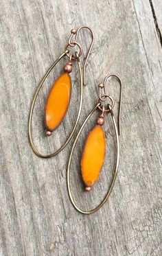 Beautiful rustic orange elongated Czech glass ovals dangle inside a hammered, antiqued copper hoop. Total hanging length approx 2.