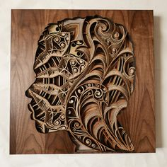Oakland-based artist Gabriel Schama continueshis adventures with his trusty laser cutter (affectionately called 'Elsie') to produce his distinct, intricate wood-relief sculptures. By layering pieces of laser-cut mahogany plywood, Schama's works are able to achieve a 3D effect, offering a patterned sense of depth. His silhouetted faces swirl with natural objects, such as sun rays and leaf motifs, but it is the architectural mastery of his geometric mandalas and layered portraits that create…