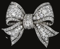 Diamond bow brooch, early 20th century. FROM THE COLLECTION OF LADY HENRIETTA ST GEORGE.  Designed as a bow, pierced and set with circular-, single-cut and rose diamonds. Sotheby's.