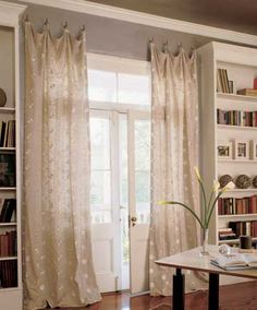 Side Steps  Long, tall sheers loop gracefully from individual hooks hung high above the door and pool slightly on the floor, creating the look of curtains drawn back from a large window.