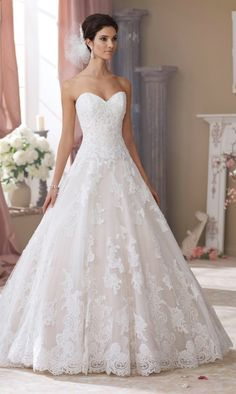 - Strapless, sweetheart neckline - Hand-beaded corded lace appliqued bodice with dropped waistline - Slightly curved back bodice with cascading covered buttons - Tulle and Organza full skirt with casc
