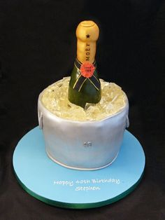 """Champagne - A huge thank you to Kelly75 for all her help and advice in making this cake!  I don't think it's as good as the one Kelly made, but my husband loved it nonetheless and it was a huge hit at his surprise party  :)  2 x 8"""" vanilla sponge cakes torted and filled with jam and buttercream, then carved for the ice bucket shape. Covered in marzipan and sugarpaste.  Bottle carved from cake.  Ice is boiled glucose syrup and sugar."""