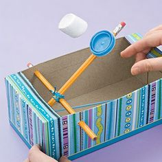 This would be fun to do for a family night. Family-size tissue box Scissors Hole punch Ballpoint pen Pushpin 2 rubber bands 2 unsharpened pencils 4-inch length of pipe cleaner Tape Plastic cap Glue dots