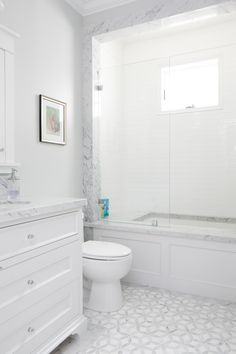 This white bathroom features a unique white and gray tile pattern, a stone slab counter top, and stone trimming around the shower.