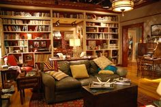 Pillows are piled haphazardly on the sofa, while the bookshelves overflow with reading material.