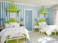 CHILD'S ROOM Wallpaper by Marthe Armitage animates the ceiling of one child's room, where a William Yeoward for Designers Guild pattern stripes the walls and a Lee Jofa floral was used for the curtains; above the bespoke Fine Arts Furniture beds are framed reproductions of vintage Vogue covers from the Condé Nast Collection and Oscar de la Renta Home for Century Furniture pagoda canopies.