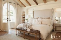 In the master bedroom, a serene and romantic space is created with muted colors and elegant linens. The designers crowned the custom bed with an upholstered headboard, and chose a tufted bench by Dovetail Furniture to place at the foot. The antique hand-knotted wool rug is from Rug Resources.