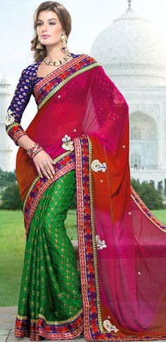 Get ready to sizzle all around you by sparkling saree.   This red, pink and green georgette and viscose saree is nicely designed with embroidered patch work is done with resham, zari and stone work.   Beautiful embroidery work on saree make attractive to impress all.   This saree gives you a modern and different look in fabulous style.   Contrasting dark blue blouse is available.   Slight color variations are possible due to differing screen and photograph resolution.