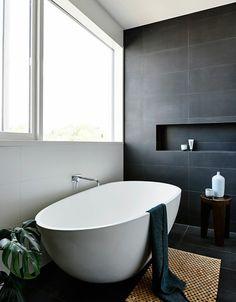 jolie baignoire ovale en blanc, sol et mur en carreaux gris anthracite, tapis en rotin