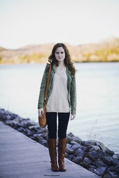 White tee + army green jacket + jeans + riding boots
