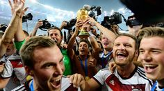 RIO DE JANEIRO, BRAZIL - JULY 13: Mesut Oezil of Germany raises the World Cup trophy with teammates Kevin Grosskreutz, Roman Weidenfeller, Shkodran Mustafi and Erik Durm after defeating Argentina 1-0 in extra time during the 2014 FIFA World Cup Brazil Final match between Germany and Argentina at Maracana on July 13, 2014 in Rio de Janeiro, Brazil. (Photo by Matthias Hangst/Getty Images)