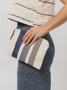"Throw it inside your tote or carry it as a clutch—it's that versatile (particularly in black & white). Please note: Due to the handwoven nature of this design, each pouch varies slightly in texture and color—and has a character all its own.8"" H x 10""W. 100% handwoven cotton. Genuine leather zipper tab. Zip closure. Handmade in Guatemala."