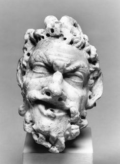 This head of Pan is carved of a fine-grained white marble that is heavily drilled. The figure has pointed ears, goat's horns, a beard, and an open mouth. Pan's head is thrust forward. The piece is broken at the neck. There is an additional break on the nose. Roman, 100 BC-AD 300