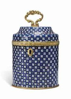 A GEORGE III BLUE-ENAMEL AND GILT-BRASS MOUNTED TEA CADDY,  STAFFORDSHIRE, CIRCA 1780 -  The blue ground decorated with white enamel and gilt flowerheads, the mounts with engraved and chased decoration, the interior with a circular matching tamper -  6.1/4 in. (16 cm.) high with handle raised