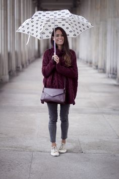 Nisi is wearing a big turtle neck sweater, cropped jeans, Superga sneakers, a burgundy cross body bag and a lips printed umbrella - teetharejade.com