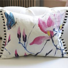 Exquisite hand painted design digitally printed on linen featuring delicate magnolia stems and a fluttering butterfly. The reverse is a cotton ticking in black and white and the cushion is trimmed with Franchini noir silk.