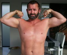 super handsome very hairy bearded man flexing biceps