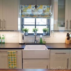 soapstone counters, deep window sill for plants, farmhouse apron sink, white subway tile, white cabinets... the colourful roman shade. I'm in kitchen heaven.