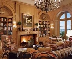 Mario Buatta ~ The pine-paneled room. Brunschwig & Fils elephant side table, floral linen and sofa chenille. John Boone sconces. Stark carpet.