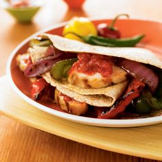 Fresh lime and garlic marinated grilled chicken paired with charred bell peppers and sweet red onion makes a tasty filling for these delicious fajitas. Top with a dollop of salsa and nonfat or low-fat plain yogurt, if you like.