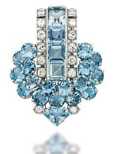AN ART DECO AQUAMARINE AND DIAMOND CLIP BROOCH, BY CARTIER Of stylised arrowhead design, the curving rectangular surmount set with a central line of square-cut aquamarines within a brilliant-cut diamond line border, to the circular-cut aquamarine cluster below with fancy-cut aquamarine and diamond point terminal, circa 1930, 4.2cm long Signed Cartier London, no.6463