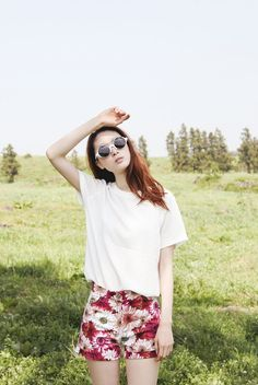 Girly and effortless summer look with the plain white tee, interesting round sunglasses, and floral printed shorts