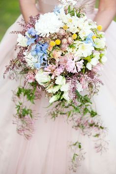 Cascading natural stem trailing bouquet featuring double tulips, Billy Buttons, hyacinth, delphinium, disbuds, blushing brides, andromeda, and lisianthus.