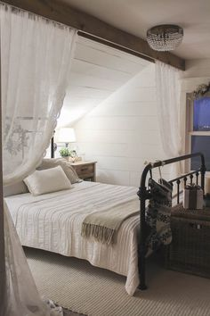 Gorgeous attached bedroom with curtain, shiplap, and iron bed.