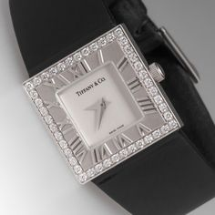 """TIFFANY & CO. 18K WHITE GOLD DIAMOND """"ATLAS"""" SQUARE COCKTAIL WATCH $7,500- From the classic Tiffany & Co. """"Atlas"""" collection, this square cocktail watch is crafted of 18K white Gold fitted with a black satin-finish strap. The face of the watch is surrounded by 44 beautiful round brilliant Diamonds. This specific watch style is no longer being sold by Tiffany, but the Atlas collection remains popular. This watch originally retailed for $10,000."""