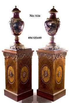 Pair of George III style Neoclassical ormolu-mounted veneer inlaid vase stands on the manner of Robert Adam, each marble topped above a frieze of ormolu beaded encadrement above richly chiseled ormolu ram's heads on each corner connected with fine cast foliate ormolu scrollworks of acanthus leaves with blossoming flowers and drapery swags of laurel wreath above a square body inlaid with sans-traverse veneer inlays ornamented with an oval paterae veneer inlay centered with and ormolu…