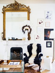 Living space with a fireplace, a vintage gold mirror, and an armchair